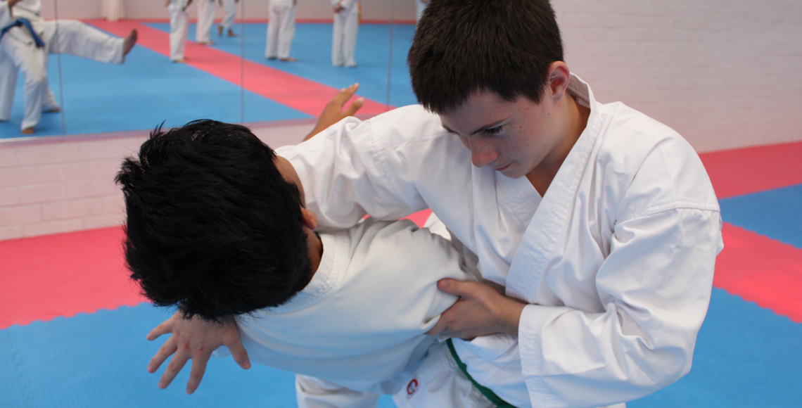 Male student practices Aiki ju justu throw